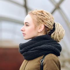Closeup portrait of young blonde woman with a dreadlocks bun