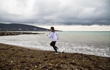 The girl runs along the beach