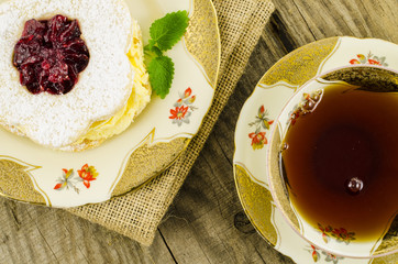 Cake with cream and porcelain tea cup