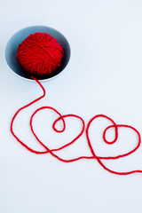 Two red hearts made from yarn, yarn ball of red and blue plate