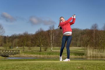 Woman golfer striking the golf ball