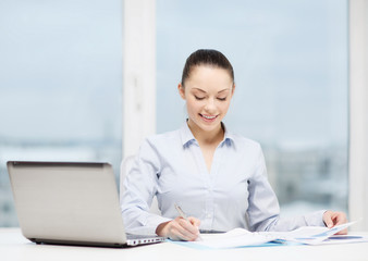 businesswoman with laptop and charts in office