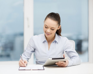 businesswoman with tablet pc and files in office