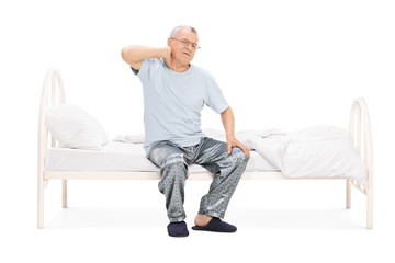 Senior feeling pain in the neck seated on a bed