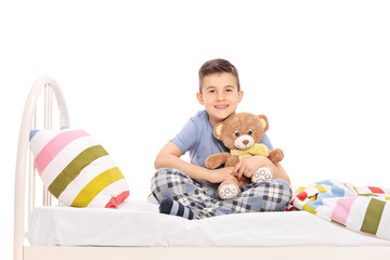 Happy little boy sitting in bed and hugging a teddy bear