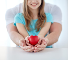 close up of man and girl holding red heart shape