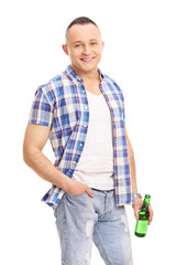Casual young guy holding a bottle of beer and posing