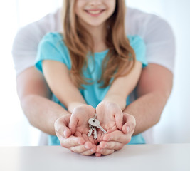 close up of man and girl hands with house keys
