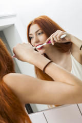 Woman Brushing her Teeth in Front a Mirror
