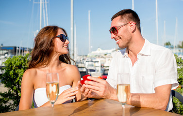 smiling couple with champagne and gift at cafe