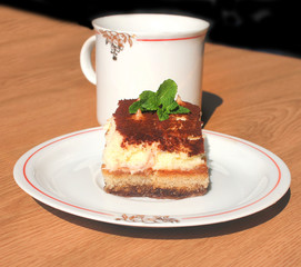 Cup of coffee and piece of cake tiramisu