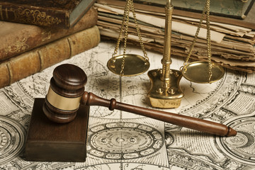 Gavel surrounded by books scale of justice and an old map