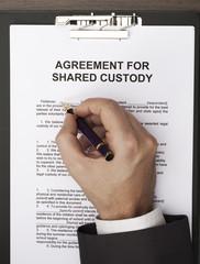 man filling agreement for shared custody document