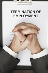 man with clasped hands over termination of employment document