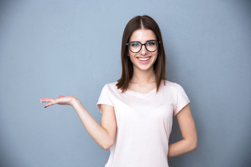 Happy young woman in glasses presenting something on the hand