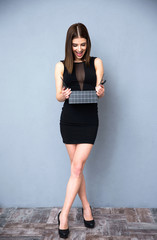surprised woman in black dress opening gift