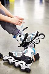 Woman wears roller skates in sports shop