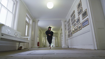 Excited female graduate in cap and gown runs through empty university hallway