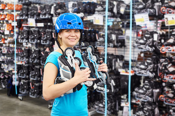 Girl in helmet and with rollers in sports shop
