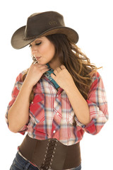 cowgirl red plaid shirt hands on bandana look down