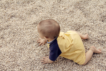 Top view of barefoot crawling infant on pebble-covered ground