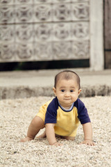 Front view of happy infant crawling on pebble-covered ground