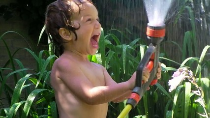 red hair, cute child playing with water hose in garden in summer