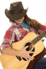 woman cowgirl with guitar looking down strumming