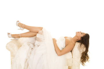 woman laying in wedding dress legs out head back eyes closed