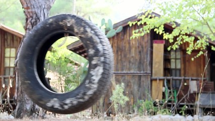swing on a tree in forest made of old tire