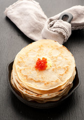 Pancakes with red caviar in frying pan