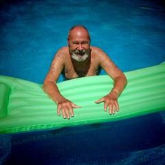 Hombre mayor en piscina con colchoneta