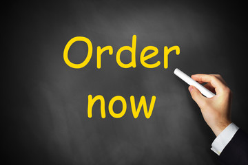 hand writing order now on black chalkboard