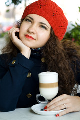 Young beautiful brunette with a delicious latte in a street cafe