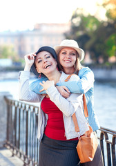 Two beautiful girls laughing and hug in the city