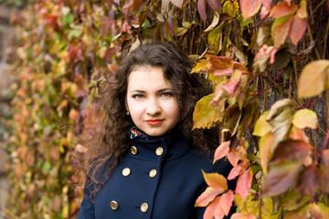 Portrait of young beautiful brunette in blue coat