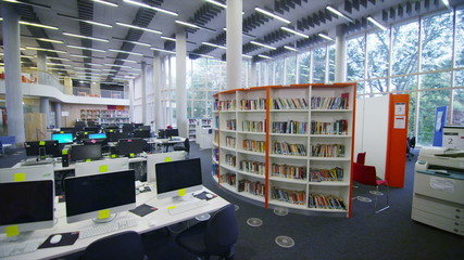 Interior view of the library in a large modern university building. No people