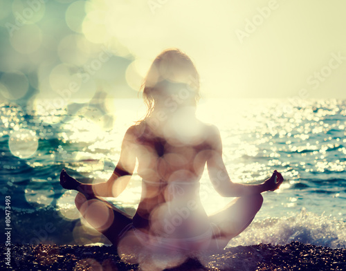 Woman Practicing Yoga by the Sea - 80473493