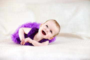 Baby girl in purple dress on white bed
