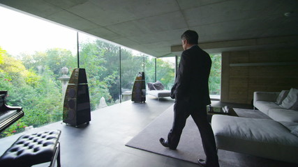 Businessman in luxury contemporary home goes to the window to look at the view