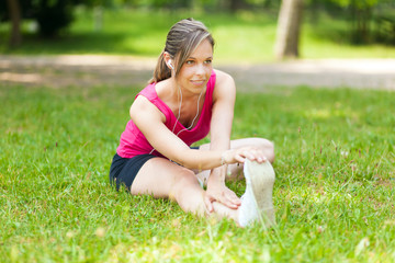 Woman stretching her leg while sitting on the grass