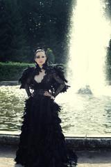 Fashion model posing next fountain in summer park