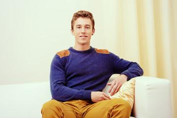 guy sits on a sofa