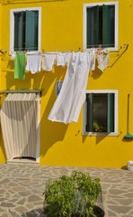 Wash clothes hanging on yellow facade in Burano, Venice, Italy