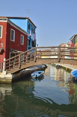 Rustic wooden bridge in canal in Burano,  Venice, Italy