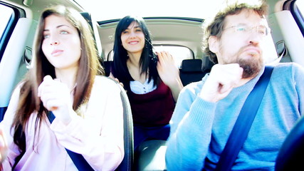 Cool women and man in car dancing and laughing