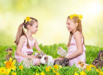 mädchen sitzen mit tierkindern auf der osterwiese