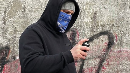 Man shaking the color spray can near the wall
