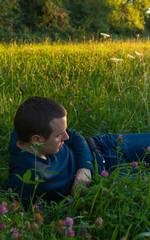 Hombre joven tumbado en la hierba con rayos de sol del atardecer