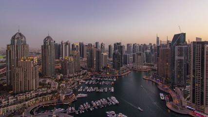 Dubai Marina with yachts in harbor and modern towers from top of